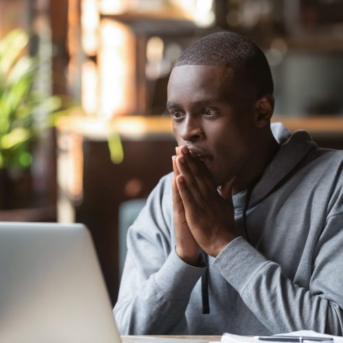 Hopeful african American guy join hands in prayer look at laptop screen read important email, black male believer receive message on computer hope for best, college admission, work promotion concept